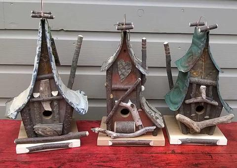 Three funky birdhouses made from drift wood and old tin ceiling tiles